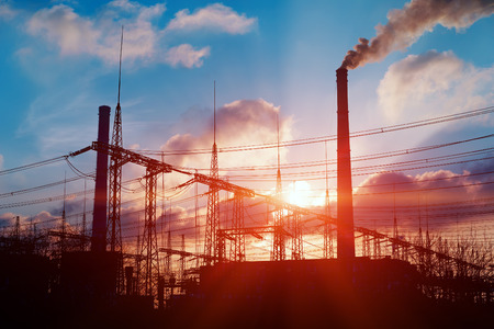 Sun setting over an electrical substation and power plant Stock Photo