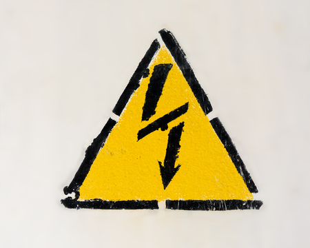 High voltage triangle warning sign mounted on gray metal wall
