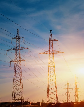 against the current: electricity pylons silhouetted against the sunset Stock Photo