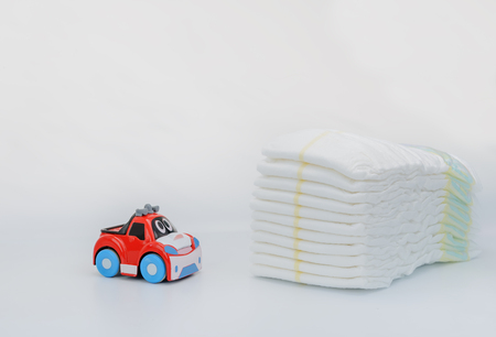 Baby Goods. Stack of Diapers. Toy car Stock Photo