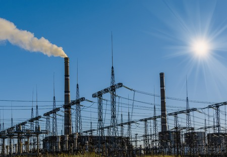 coal power plant with chimney and the sun