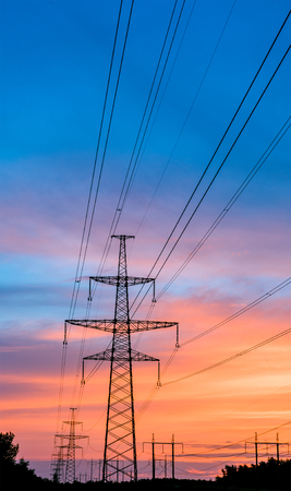over voltage: silhouette engineer repair and electrical installation work on high voltage pylons over Stock Photo