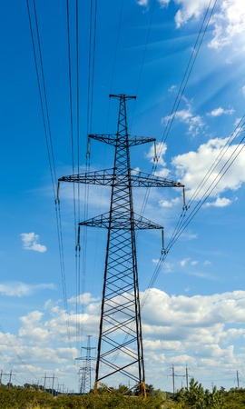 Electricity pylon silhouetted against blue sky background. High voltage tower. Stock Photo