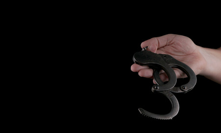 steel handcuffs of police special equipment, fetters on a black background Stock Photo