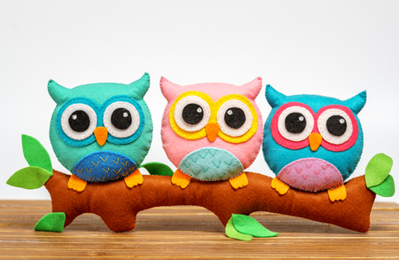 toy owls handmade on a branch. light background