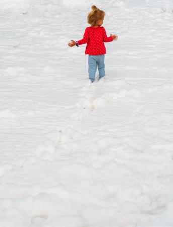 A child runs through the snow. Winter vacation. The kid runs through the snowdrifts