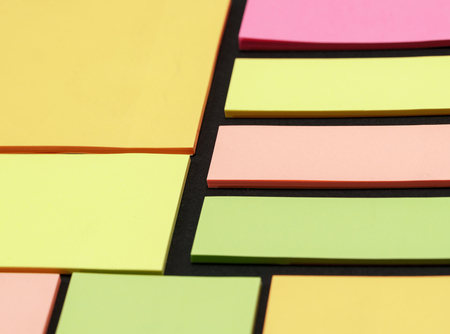 Blank note paper set of different colours forms and sizes. Sticky notes collection on black background.