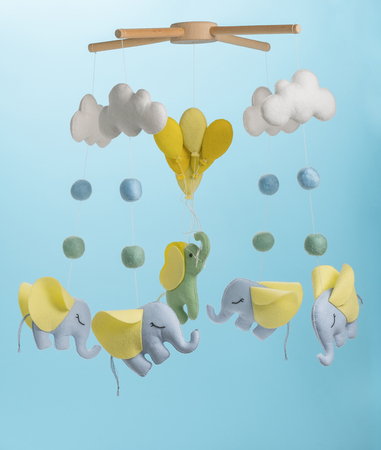 Colorful and eco-friendly children's mobile from felt for children. It consists of elephant, clouds and balloons toys. Handmade on blue background.