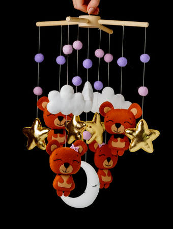 Colorful and eco-friendly childrens mobile from felt for children. It consists of bears, stars,moon, clouds and balloons toys. Handmade on black background. Stock Photo