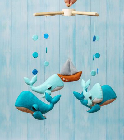Colorful and eco-friendly children's mobile from felt for children. It consists of dolphins, ship and balloons toys. Handmade on blue background made from wood.