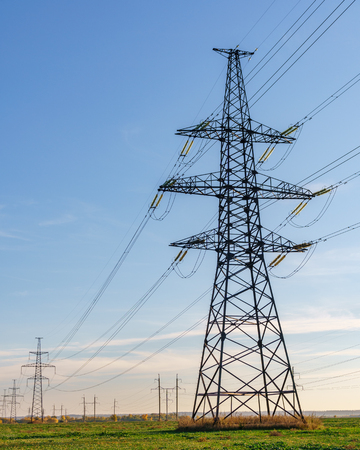 Supports high-voltage power lines against the blue sky. Electrical industry