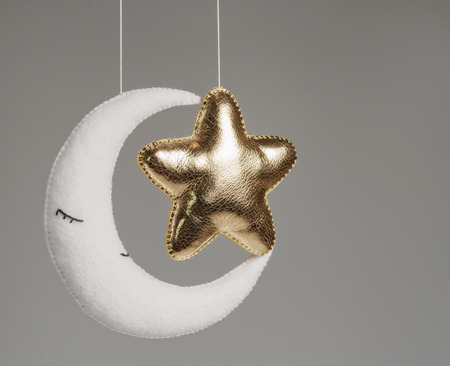 A felt toys in the form of a golden star and moon , part of a children's mobile. On a gray background. Colorful and eco-friendly children's mobile from felt for children.