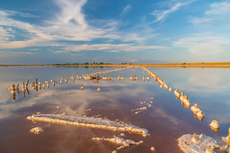 salt lake at sunset, the ancient method of extraction of salt from the sea, alien landscape, snow in the summer, pastel pink tones and gradients