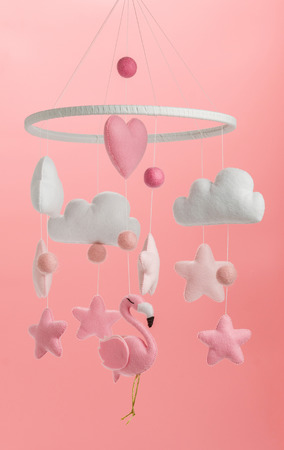 Colorful and eco-friendly children's mobile from felt for children. It consists of flamingo toys, clouds, stars and balloons. Handmade on pink background. Stock fotó - 122255149