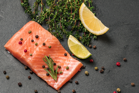 Raw salmon fillet on a dark slate background. Trout fillet with thyme, lime and peppercorns. Wild atlantic fish close up. Healthy food.