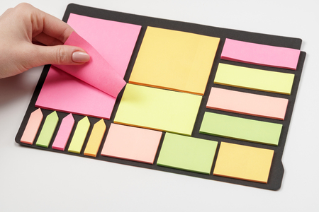 Blank note paper set of different colours forms and sizes. Sticky notes collection on black background. Female hand tear off paper note.