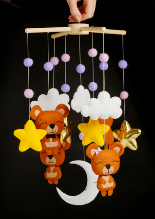Colorful and eco-friendly children's mobile from felt for children. It consists of bears, stars,moon, clouds and balloons toys. Handmade on black background.