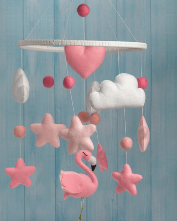Colorful and eco-friendly childrens mobile from felt for children. It consists of flamingo toys, clouds, stars and balloons. Handmade on blue background made from wood.