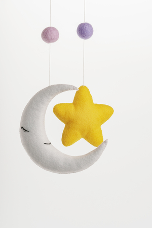 Colorful and eco-friendly children's mobile from felt for children. It consists of moon and star toys. Handmade on white background.