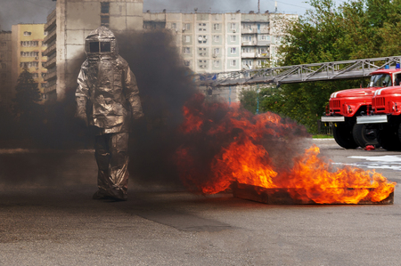 Fiteman in a fire proximity suit puts on fire.Fireman in a fire proximity suit which made to protect him from hazardous materials and when he extinguishes the fire.