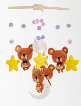 Colorful and eco-friendly children's mobile from felt for children. It consists of bears, stars,moon, clouds and balloons toys. Handmade on gray background.
