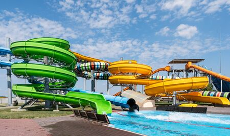 Water park, bright multi-colored slides with a pool. A water park without people on a summer day with a beautiful, cloudy blue sky. Stock Photo