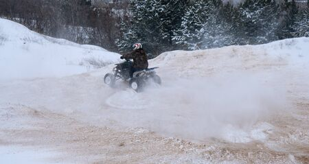A motorcyclist on an ATV rides off-road in a snowy winter forest.