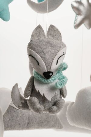 A felt toy in the form of a lovely fox, part of a children's mobile. On a white background. Colorful and eco-friendly children's mobile from felt for children. Stock Photo