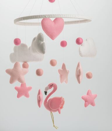 Colorful and eco-friendly childrens mobile from felt for children. It consists of flamingo toys, clouds, stars and balloons. Handmade on white background.