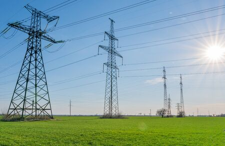 High voltage lines and pylons and a green agricultural landscape on a sunny day. Association of agriculture and industry in one photo. Beautiful spring landscape of the European plain.