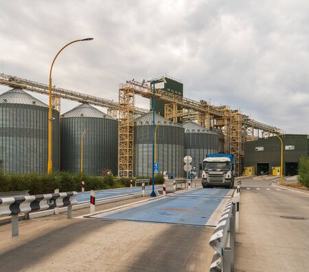Modern elevator for storing grain against the sky. Grain drying complex, storage and transportation of grain. Large granary in the field. Agricultural industry.