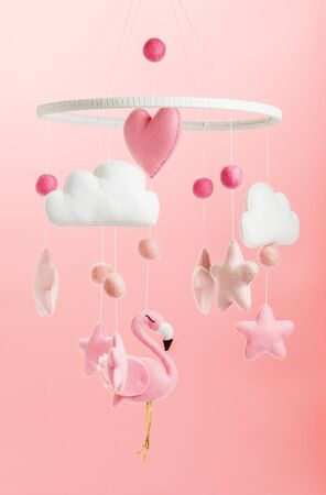 Colorful and eco-friendly childrens mobile from felt for children. It consists of flamingo toys, clouds, stars and balloons. Handmade on pink background. Zdjęcie Seryjne