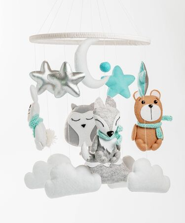 Colorful and eco-friendly childrens mobile from felt for children. It consists of bear, fox, owl, rabbit, mountain, stars, clouds and balloons toys. Handmade on gray background.
