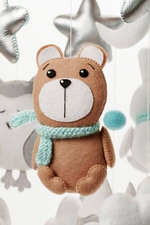 A felt toy in the form of a bear, part of a childrens mobile. On a white background. Colorful and eco-friendly childrens mobile from felt for children.