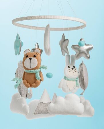 Colorful and eco-friendly childrens mobile from felt for children. It consists of bear, fox, owl, rabbit, mountain, stars, clouds and balloons toys. Handmade on blue background.