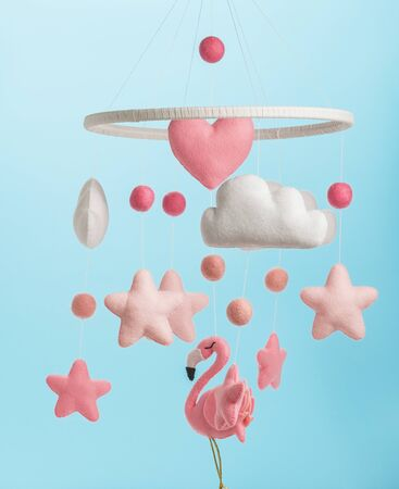 Colorful and eco-friendly childrens mobile from felt for children. It consists of flamingo toys, clouds, stars and balloons. Handmade on blue background.