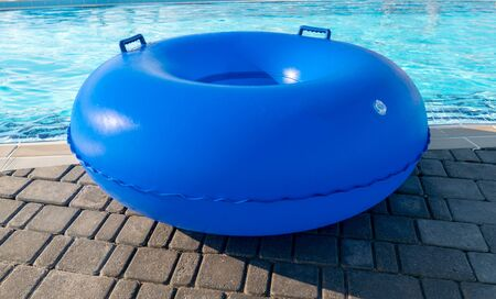 Yellow pool float, ring floating lying by the refreshing swimming pool. Inflatable ring lying by the pool on a sunny day.