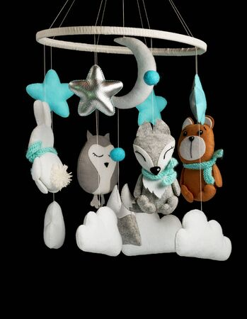 Colorful and eco-friendly childrens mobile from felt for children. It consists of bear, fox, owl, rabbit, mountain, stars, clouds and balloons toys. Handmade on black background.
