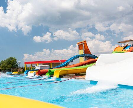 Parque acuático al aire libre. Toboganes y piscinas multicolores. Nadie.