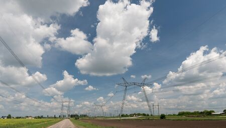 Electrical net of poles on a panorama of blue sky and green meadow. 版權商用圖片