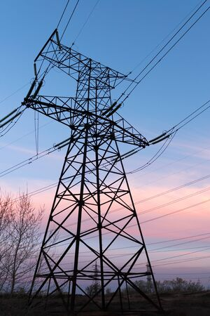 The silhouette of the evening electricity transmission pylon. Power transmission from a power plant to a city