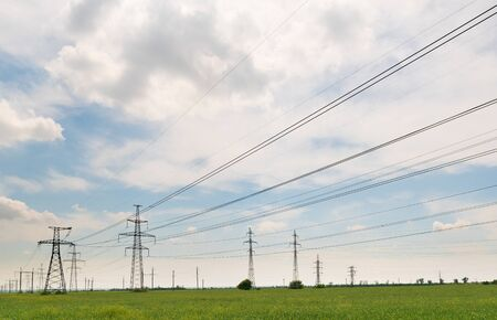 High voltage power lines leading through a green field. Transmission of electricity by means of supports through agricultural areas. 版權商用圖片