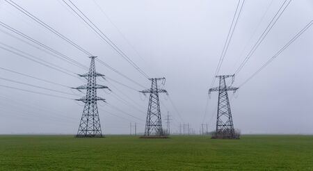 Electric network of pylons against a cloudy sky and a green meadow.