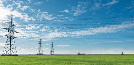 Electrical net of poles on a panorama of blue sky and green meadow. 스톡 콘텐츠