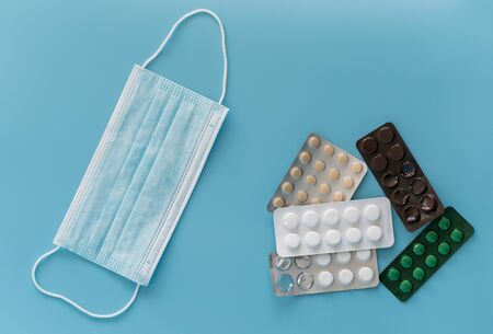 Medical mask and pills on a blue background. Protection against viruses and bacteria. Respiratory disease. 스톡 콘텐츠