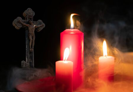 Candles in smoke with a cross on a black background with a cross 스톡 콘텐츠