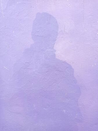 The shadow of a man who falls on a purple wall.