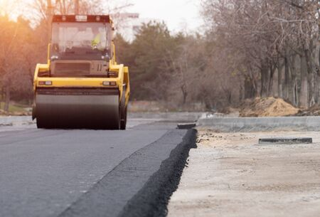 The vibratory roller levels the asphalt pavement. Standard-Bild
