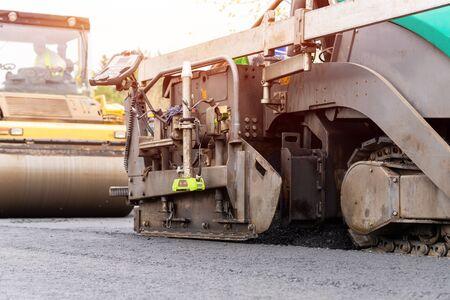 Green asphalt paver for road construction.
