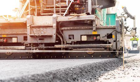 Paver machine is laying fresh asphalt on city road.